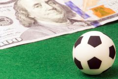 Macro. A soccer ball on a green background and a hundred-dollar bill. Concept money and sports, betting on football, a player`s s Royalty Free Stock Photography
