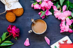 The concept with morning coffee in a romantic style on the black wooden background. Peonies flowers and petals, cookies, mug with Stock Image