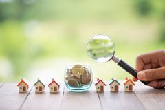 Concept of a mortgage, a coin, a model of a house and a magnifying glass, house and money. magnifying glass and coins,. Construction, rental housing stock photography