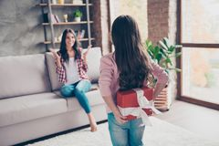 Concept of mother`s day. Little girl is hiding a red giftbox beh. Ing her back, surprised cheerful happy mother is sitting on a couch on the background Stock Image