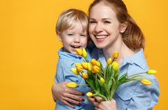 Concept of mother`s day. mom and baby son with flower on colored Royalty Free Stock Photo