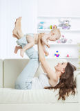 Concept of motherhood:happy mother playing with one year old baby in the room for children. Happy young mother playing with cute one year old baby in the room Royalty Free Stock Photos