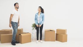 Strong man is carring a large moving box, full of items, isolated on white background. 4K. Concept moving. Man is drawing up a black item from a large box stock video footage