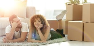 Concept of moving to a new home. Happy couple lying on the floor. Happy couple lies among the uncleared boxes in the new apartment Stock Images