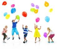 Concept multi-ethnique d'amitié de bonheur de ballon d'enfants Photographie stock libre de droits