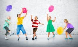 Concept multi-ethnique d'amitié de bonheur de ballon d'enfants Photographie stock