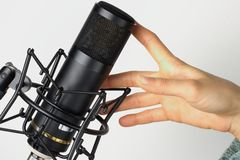 Studio microphone with hand. Concept of music: Studio microphone with hand Stock Photo