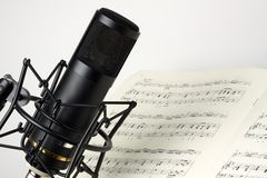 Studio microphone with music sheet. Concept of music: Studio microphone with music sheet royalty free stock image