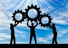Concept of mutual benefit. Silhouette of the three men holding the gears put them together in one gear. The concept of mutual benefit Stock Photo
