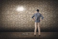 Concept of mystery, problem, solution. Asian man standing in front of a puzzle wall. Concept of mystery, problem, solution Stock Photography