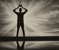 Concept of narcissism and selfishness. Silhouette of a selfish and narcissistic man reconciling his own crown Stock Image