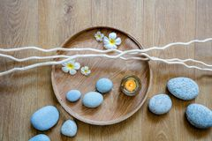 Concept of natural female flow and rhythm with ayurveda spa. Decor composed of beautiful pebbles, candle, fresh flowers and twigs over round wooden tray, above stock photography