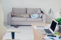 Concept of necessity of having a rest while working. Tired exha. Usted manager clothed in formal-wear is sleeping on a sofa in his modern office royalty free stock photo