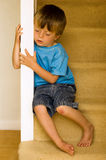 Concept of neglected child. Sitting on a carpeted stairway Stock Photography