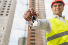 Concept of new home. Engineer on building site showing key from Royalty Free Stock Photos