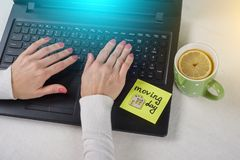 The concept of new housing, moving. A note of text Moving Day written on the paper sticker. Laptop, computer woman`s hands backgr Royalty Free Stock Images