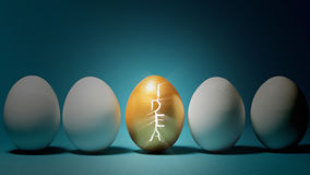 Concept a new idea. Shell of the golden egg is cracked in the form of the word `idea`, which symbolizes the birth of a new idea. On blue background stock image