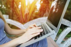 Thailand, Phuket travel close up woman hand fingers press laptop keyboard for remote work on sunny day, background of stock photos