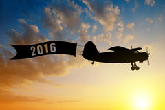 Concept of New Year 2016. Engine airplane flying at sunset. Concept of New Year 2016 Stock Photography