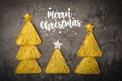 Concept of new year from mexican nachos. Christmas trees made of chips nachos with cheese on a dark background. Copy space stock photo