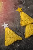 Concept of new year from mexican nachos. Christmas trees made of chips nachos with cheese on a dark background. Copy space royalty free stock image