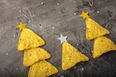 Concept of new year from mexican nachos. Christmas trees made of chips nachos with cheese on a dark background. Copy space royalty free stock photos