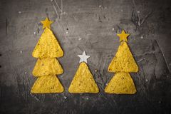 Concept of new year from mexican nachos. Christmas trees made of chips nachos with cheese on a dark background. Copy space royalty free stock photo