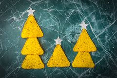 Concept of the new year from the Mexican nachos. Christmas trees made of nacho chips with cheese on a blue background. Copy space royalty free stock images