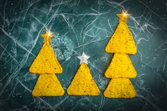 Concept of the new year from the Mexican nachos. Christmas trees made of nacho chips with cheese on a blue background. Copy space stock images