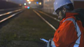 Concept of night shift. Worker in helmet using smartphone in the twilight.4k. Concept of night shift. Worker in hard helmet using smartphone in the twilight stock video