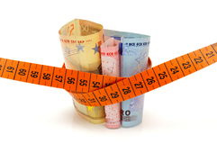Concept od cutting cost with money and measuring tape Royalty Free Stock Photo