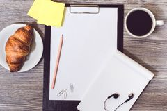 Concept of office accessorise lying on wooden desktop: clipboard. Croissant, cup of coffee, earphones Stock Image