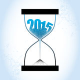 Concept of the 2015 old year with hourglass and decreasing sand on the textured blue background.  Royalty Free Stock Image