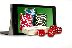 The concept of online gambling, dice, chips, and cards on the background of the tablet royalty free stock photography