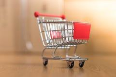 Concept online het winkelen: Weinig boodschappenwagentje op leveringsdozen stock afbeeldingen
