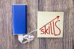 Concept of online learning methods. Charging bank with concept of upgrading online skills. Handwritten word skills on the white pa. Concept of online learning stock photos