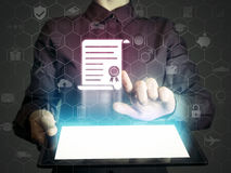 Concept of online learning. Person touches to certificate icon diploma. She holds tablet pc, that contains a many different online services royalty free stock image