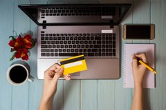 Concept of online new technologies, shopping buy goods. Woman buying with debit credit card and laptop in cafe. Top view. Flat lay stock photos