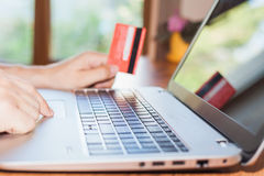 Concept of online payment by plastic card through the Internet Banking. Close-up of human hand for laptop and holding credit card, man is shopping indoor at Royalty Free Stock Photo