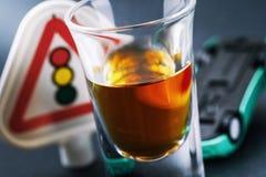 Concept op het onderwerp van het drijven terwijl bedwelmd Een glas van whisky en een omgekeerde auto stock afbeelding