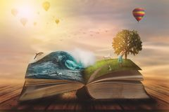 Concept of an open magic book; open pages with ocean and land and small child. Fantasy, nature or learning concept, with copy