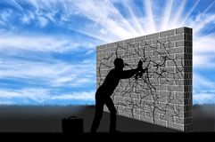 The concept of overcoming challenges in business. A silhouette of a businessman breaks the wall with your hands . The concept of overcoming challenges in royalty free stock image