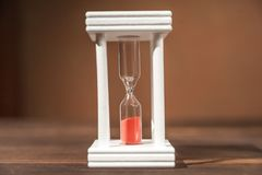 The concept of passing time. White hourglass with red sand inside on a wooden textural background. The concept of passing time. White hourglass with red sand stock image