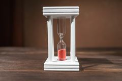 The concept of passing time. White hourglass with red sand inside on a wooden textural background. The concept of passing time. White hourglass with red sand royalty free stock image