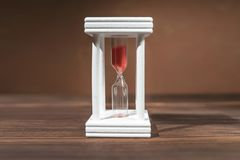 The concept of passing time. White hourglass with red sand inside on a wooden textural background. The concept of passing time. White hourglass with red sand stock images