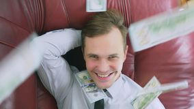 The concept of passive income. a happy person is lying on the couch and smiling, dollars on top of him are falling. 4k. Close-up slow-motion stock video