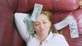 The concept of passive income. happy woman lies on the couch and smiles, on top of her falling dollars. 4k, close-up. Slow-motion stock footage