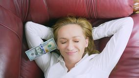 The concept of passive income. happy woman lies on the couch and smiles, on top of her falling dollars. 4k, close-up. Slow-motion stock video footage