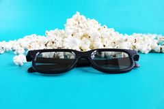 Concept pastime, entertainment and cinema. Popcorn and 3d glasses on light blue background royalty free stock photos