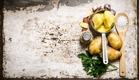 The concept of a peeled potato in the pot on the rustic background . Free space for text. Royalty Free Stock Image